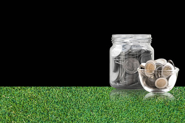 coins in a glass jar on grass floor ,savings coins - Investment And Interest Concept saving money concept, growing money on piggy bank. isolated on black background