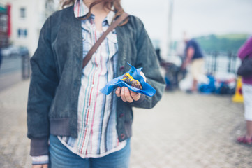 Woman holding tasty sausage in the street