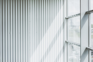 Background. Modern interior. Loft style. White corrugated wall with vertical stripes. Next to the wall window with a metallic sash.