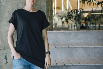 Girl standing in room with modern interior next to seating with wooden texture,on background of concrete wall.Young woman dressed and black T-shirt and blue jeans,in hand of girl smartwatch. Mock up.