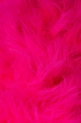 Pink plush fabric vertical. Very soft polyester textile made of synthetic fibers with long hairs. Macro close up material photography.