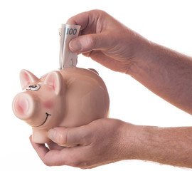 A male hand dropping 100 SEK into a piggy bank isolated on white background