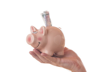 A man holding a piggy bank with 100 SEK isolated on white background