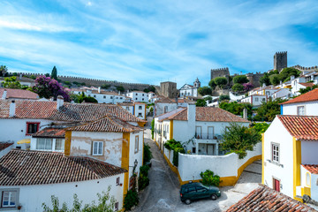 Obidos, Portugal : Cityscape of the town with medieval houses, wall and the Albarra tower. Obidos is a medieval town still inside castle walls, and very popular among tourists.