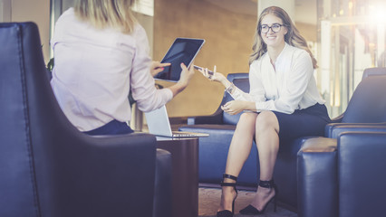 Two young business women sit opposite each other and talking,the first woman sits with his back to the camera,holding a tablet computer, other woman in white blouse smiling and holding a smartphone.