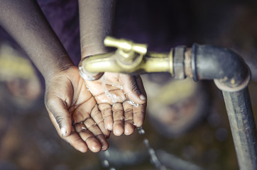 African Child with Hands Cupped under Water Tap in Bamako
