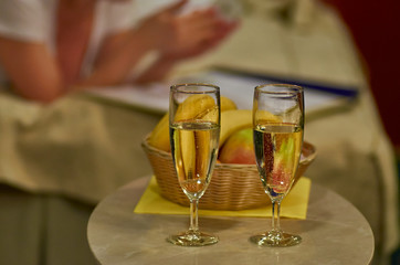 Two glasses of sparkling wine in hotel room with woman in backgr