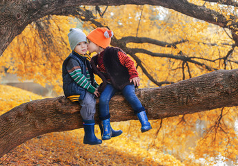 Little boy and girl kissing on a branch of tree in autumn forest