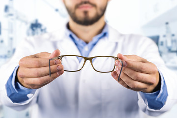 eyesight care concept - optician giving new optical glasses