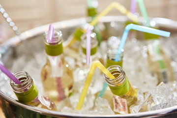 bottles with tasty drink in ice. Shallow dof