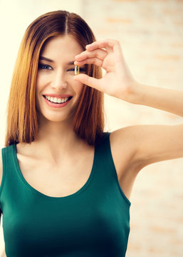 Smiling woman with Omega 3 fish oil capsule