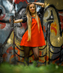 beautiful girl with long hair in a red dress on  background of graffiti