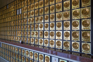 Wall full of gold-framed drawers that contain ashes of the deceased, each with image of a Buddha in the columbarium at the Ten Thousand Buddhas Monastery (Man Fat Tsz) in Sha Tin, Hong Kong, China.