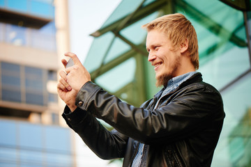 The blond guy with a beard in a leather jacket and shirt, takes pictures with a mobile phone in the background the building with a glass facade