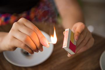 Closeup of female hands lighting a match on box with flame and plates