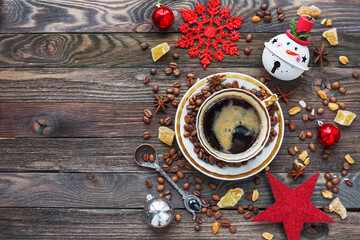 Rustic wooden background with cup of coffee and New Year decorations. White vintage dinnerware and...