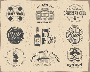 Set of vintage handcrafted pirates emblems, labels, logos. Isolated on a scratched paper background. Sketching filled style. Pirate and sea symbols - old rum bottles, barrels, skull, pistol. Vector