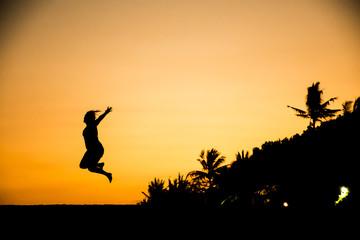 Bali jumping girl silhouette Sanur Beach sunset