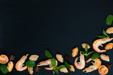 Preparing fresh seafood in the kitchen with gourmet pink shrimp and mussels surrounded by fresh herbs and spices on black stone background
