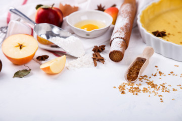 Baking Background. Ingredients  for baking Apple Pie  - apples,spices ,flour,  rolling pin, eggs, egg yolks, butter served, milk on white background.selective focus. Copy space.
