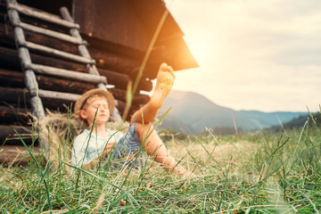 Boy sleeps in grass under hayloft in summer afternoon