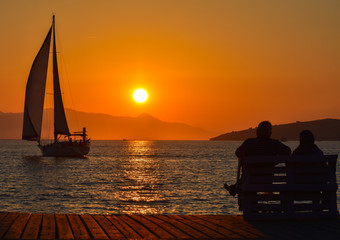 Sailing boat on the sea at sunset. Old couple sitting on a bench near the sea.