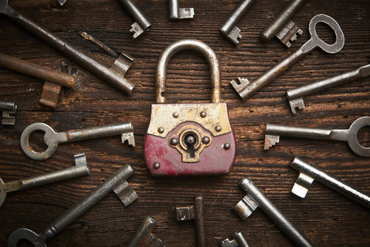 Vintage rusty padlock surrounded by old keys on a weathered steel background