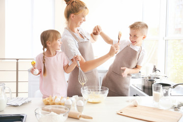Mother and kids in kitchen making dough