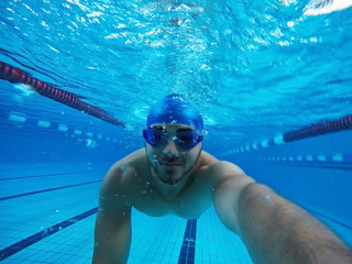 Young man swimming underwater in pool