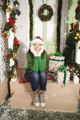 pretty happy smiling young teenage hipster girl infront of decorated for Christmas house, waiting for guests coming, winter snow around, lifestyle people concept on holiday