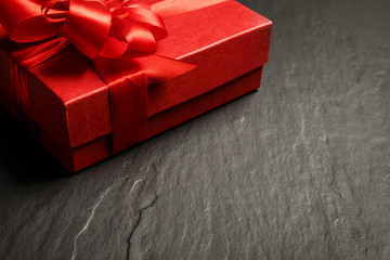 Red gift box with ribbon on dark stone background with copy space, vintage look