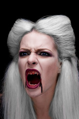 Beautiful blonde girl vampire is screaming. The blood is on the mouth.