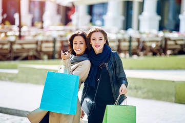 Two happy girls girlfriend doing shopping in the city