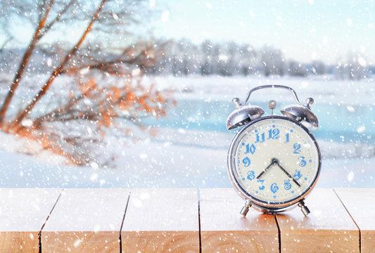 Vintage retro alarm clock in snowy weather