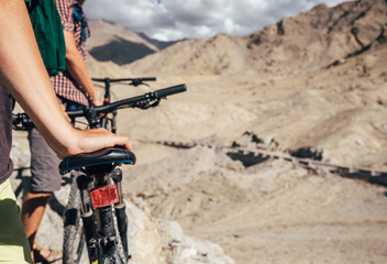 Close up image man hand on bicycle saddle. Two maountain bikers