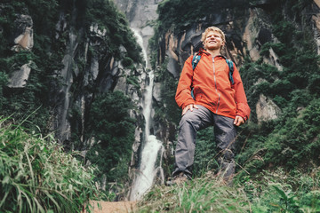 Young tourist man stay in mountain near the waterfall