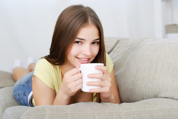 young woman sitting on couch and drinking coffee