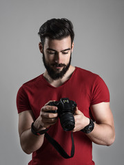Young bearded photographer reviewing photos on rear lcd screen of dslr camera. Moody desaturated portrait over gray studio background.