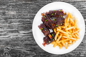 fried sticky ribs sprinkled with green onion with french fries