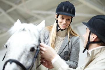 Fototapeten Reiten Image of young woman sitting on the horse and looking at instructor