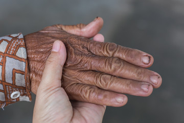 young person holding old hand