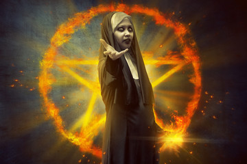 Devil nun woman standing in front of burning pentagram with magic spell