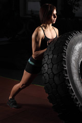 Fit female athlete performing a tire flip