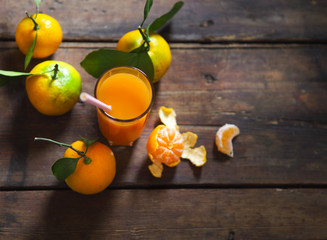 Glass of fresh tangerine juice with ripe tangerines