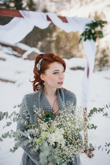 Young attractive bride with the bouquet over snowy nature backgr
