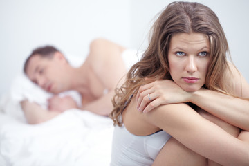Dissatisfied woman sitting by bed where her husband is sleeping