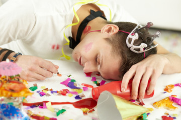 Young man in party hat sleeping on table among confetti and remnants of food