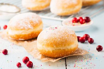 Delicious freshly baked doughnuts with powdered sugar and fruit jam on blue wooden background. Selective focus.