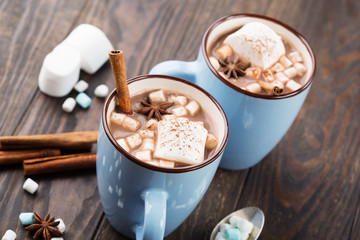 Blue Cups of hot Chocolate drink with Marshmallows and cinnamon on dark wooden background. Winter time. Holiday concept, Selective focus