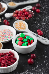 Christmas baking cupcake decorations and sprinkles, black background, selective focus. Holiday concept